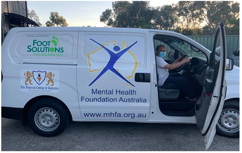 A man is sitting in a van with the Mental Health Foundation Australia logo
